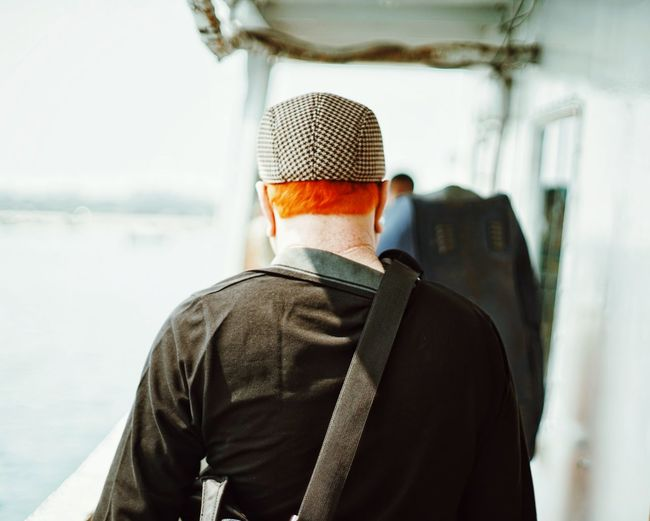 Rear View Of Redhead Man Walking On Boat