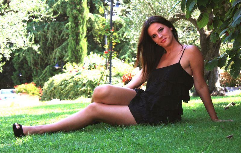 Portrait Of Beautiful Young Woman Wearing Dress While Sitting On Grassy Field At Park