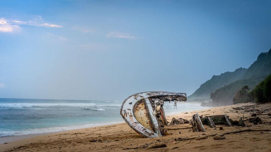 Shipwreck On Beach Against Sky
