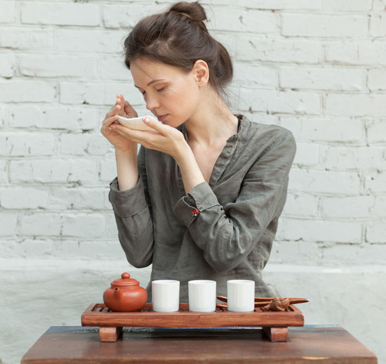 Young woman preparing green tea while sitting against wall