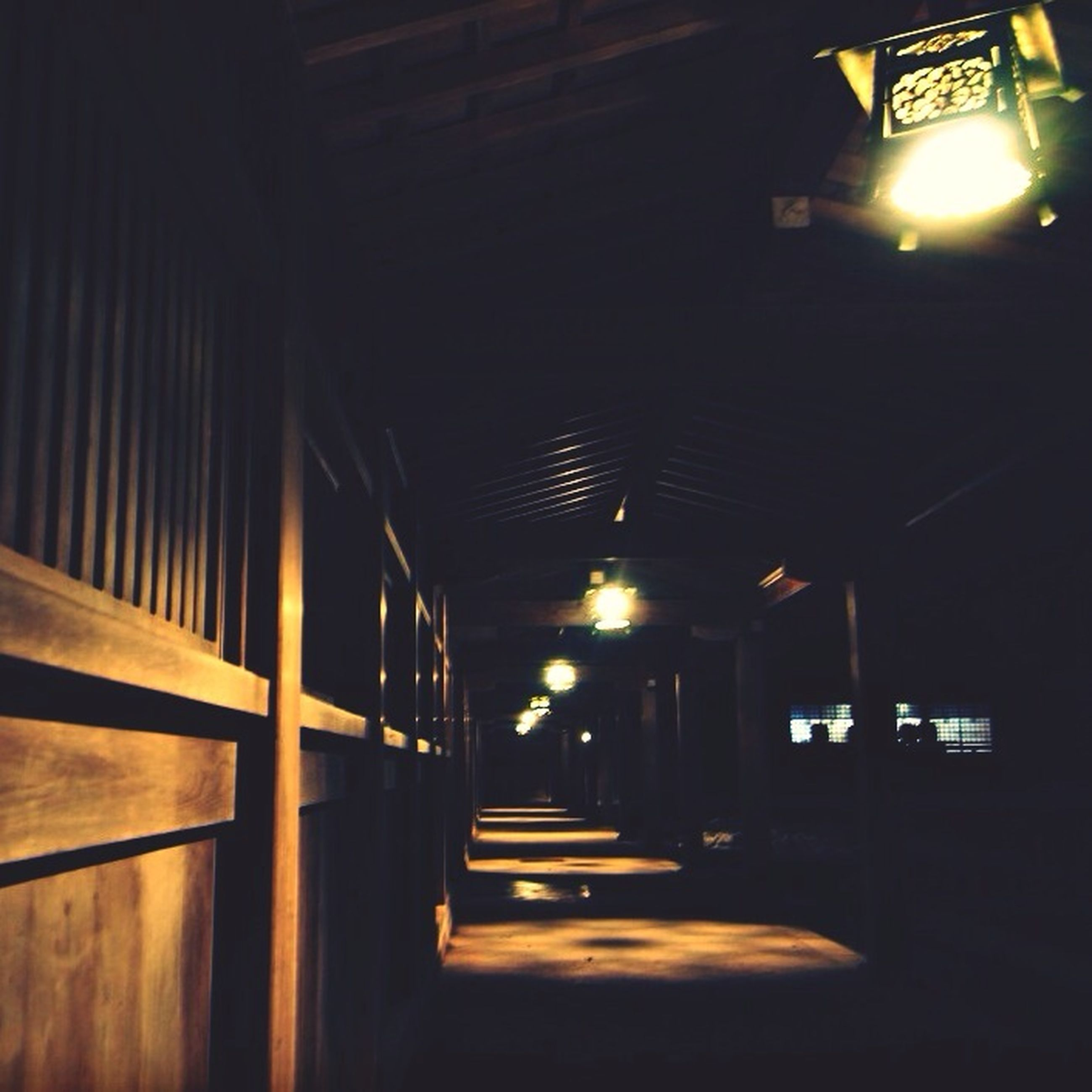 indoors, illuminated, built structure, architecture, lighting equipment, ceiling, interior, corridor, architectural column, night, light - natural phenomenon, empty, the way forward, absence, column, entrance, wood - material, door, no people, electric light