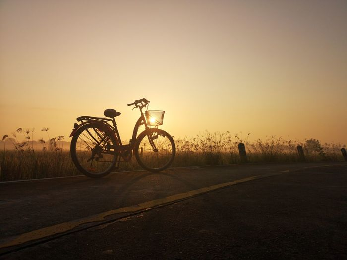 Bicycle on street against clear sky during sunset