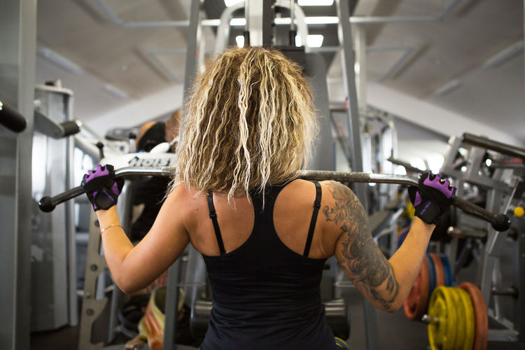 Rear view of woman with tattoo on back exercising at gym