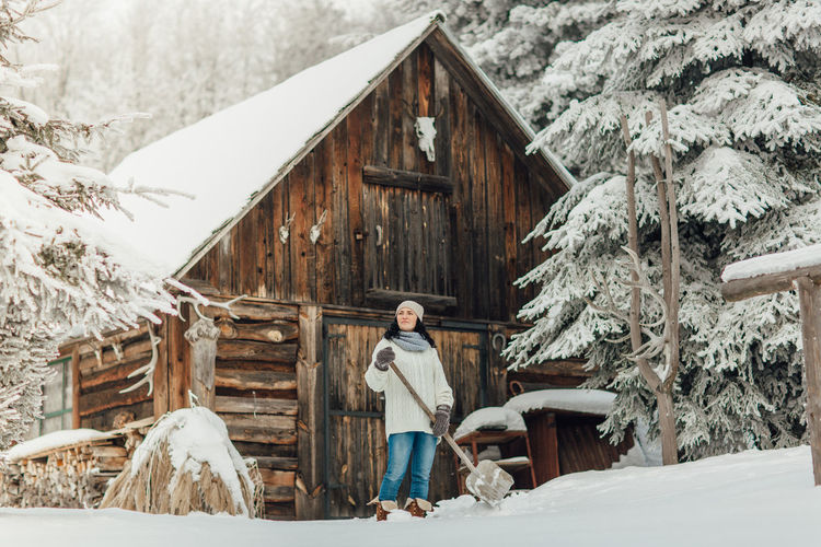 Smiling young woman looking away while standing on snow field by cottage
