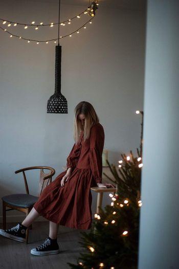 Woman looking at illuminated christmas lights at home