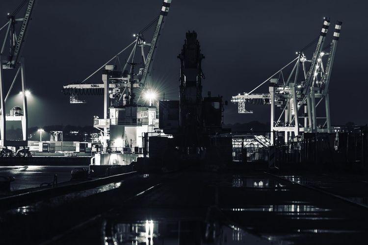 Illuminated cranes in harbor on sea at night