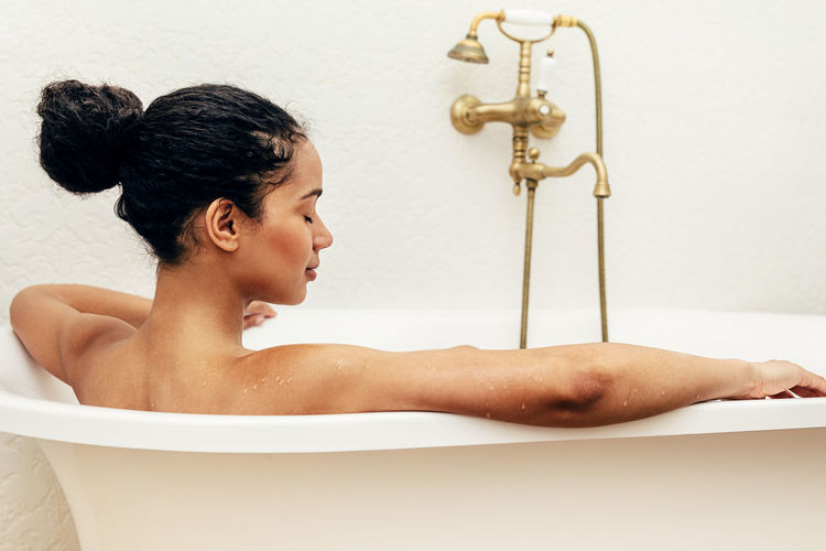 Bathtub Domestic Bathroom One Person Bathroom Indoors  Taking A Bath Home Hygiene Lifestyles Real People Side View Relaxing Evening Skin Care Body Care African American Lying Domestic Room