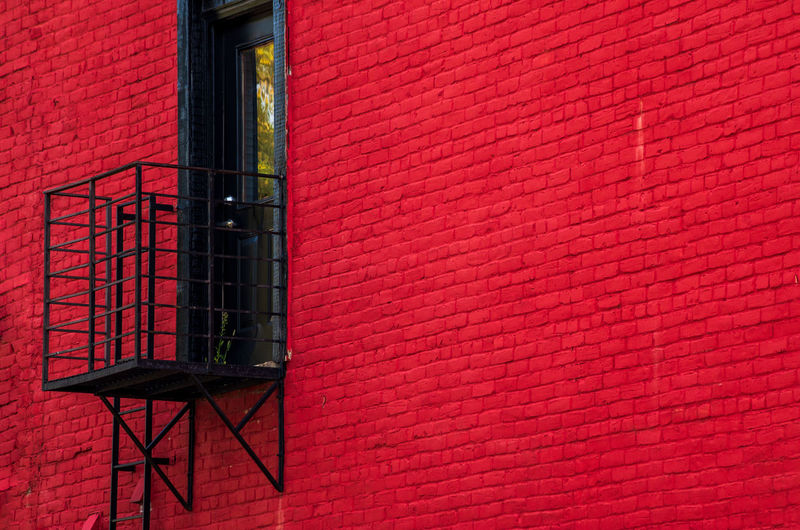 Architecture Brick Brick Wall Building Building Exterior Built Structure Day Fire Escape Low Angle View Metal No People Outdoors Pink Color Pipe - Tube Red Residential District Safety Wall Wall - Building Feature Window