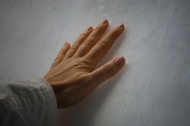 Cropped Hand Of Woman Touching White Wall