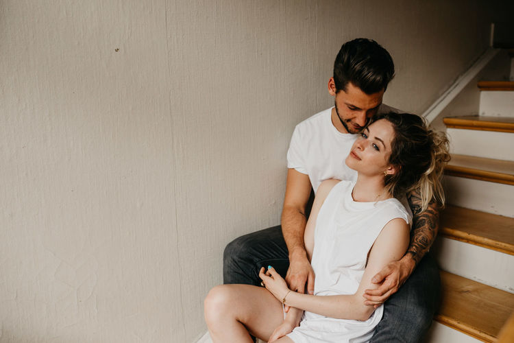 Young couple sitting against wall