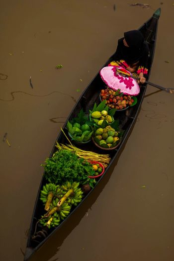 High angle view of person selling fruits in boat on canal