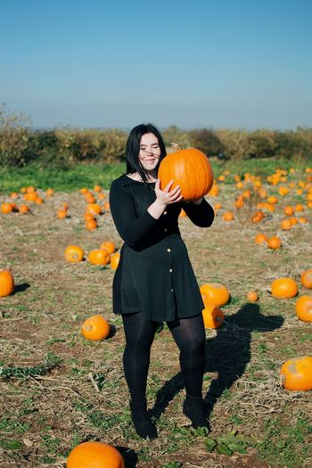 Pumpkin Food One Person Food And Drink Nature Halloween Plant Holding Sky Smiling Field Land Leisure Activity Outdoors Women Full Length Day Orange Color Autumn Standing
