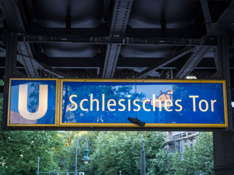 Schlesisches Tor subway station sign with shoe hanging from it Berlin Kreuzberg Low Angle View Metro Schlesisches Tor Shoe U-Bahn U1 Blue Capital Letter Communication Day Guidance Information Information Sign Metal Mode Of Transportation No People Outdoors Sign Subway Subway Station Text Transportation Western Script
