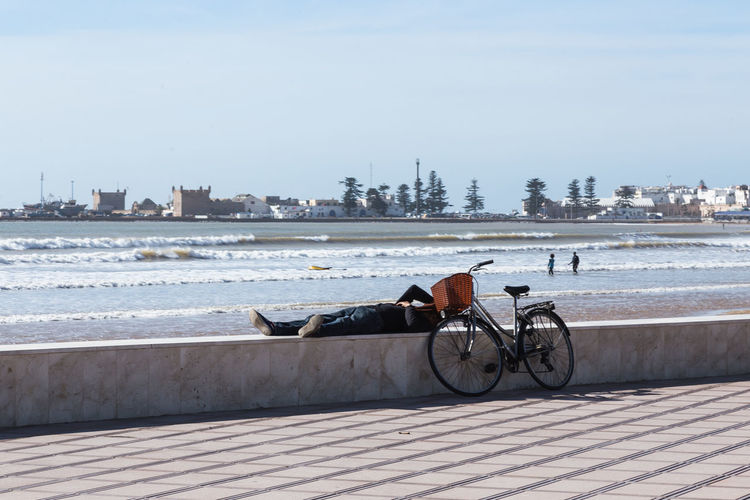 Man with bicycle lying on retaining wall against