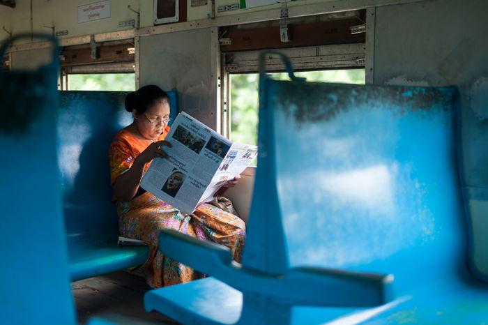 Burmese lady reading newspaper inside the train. Article Blue Editorial  Lady Media Myanmar News Newspaper People Photojournalism Read Train Wanderlust Women Yangon