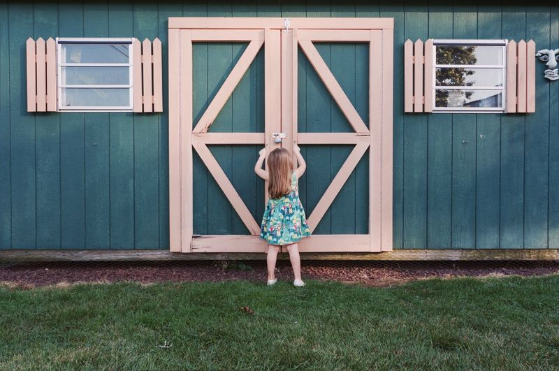 Full length of boy standing against built structure
