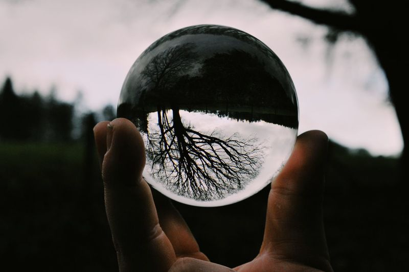 Close-up of person holding crystal ball against sky