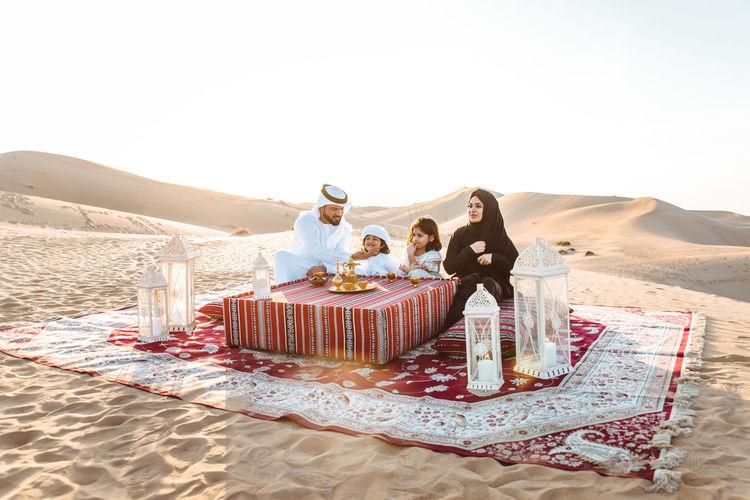 Happy family sitting carpet at desert