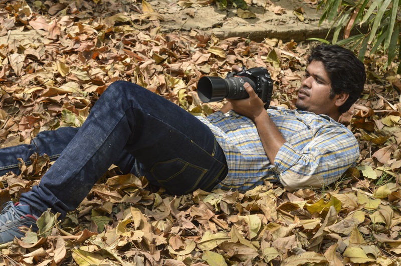 Side view of young man photographing autumn leaves on land