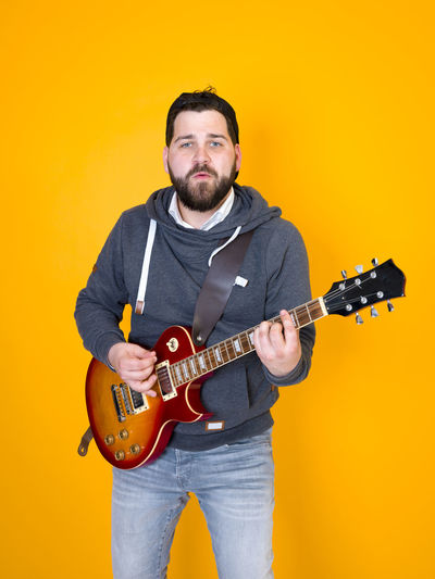 man with black hair and beard playing the electric guitar in front of a yellow background Guitar Electric Man Hair Beard Black Musician Playing Musical Instrument Hoodie Singing Singer  Entertainer Single Solo Entertainer Star Artist Art Profession Model Portrait Pose Jeans Yellow Orange Copy Space Fun Happy Lifestyle Learn Funny Solo Rock Guitar Valuable Band Sheet Music Song Music Rehearsal Modern Cool Front View One Person Studio Shot Standing Musical Equipment String Instrument Three Quarter Length Indoors  Colored Background Casual Clothing Arts Culture And Entertainment Adult Yellow Background Electric Guitar Rock Music