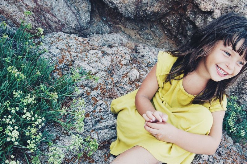 High angle view of cute smiling girl sitting on cliff
