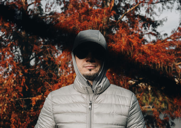 Man wearing hooded shirt while standing against trees