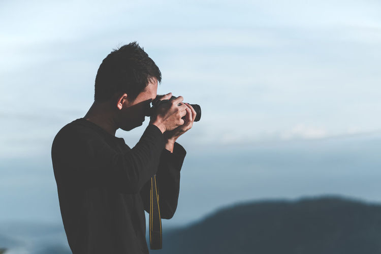 Side view of young man photographing with digital camera against sky