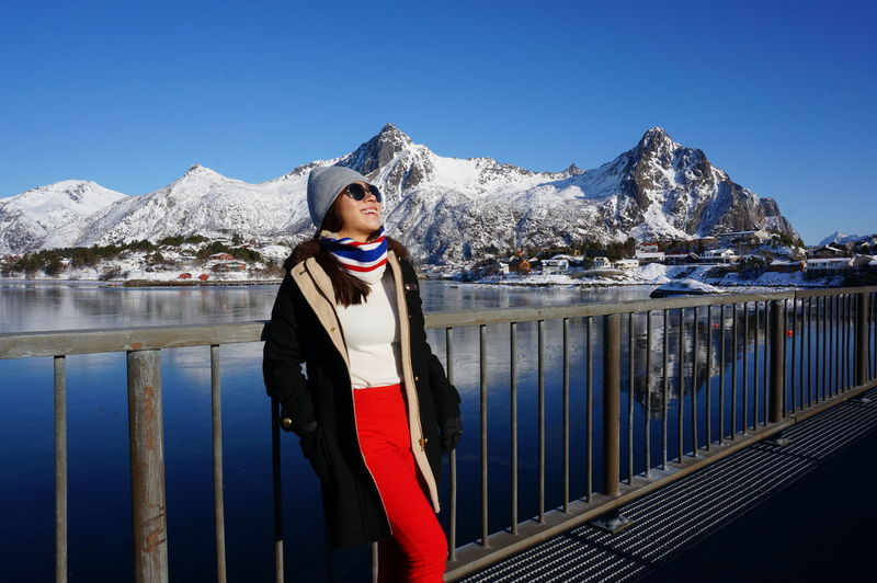 Full Length Of Woman Standing Against Snowcapped Mountain By Lake