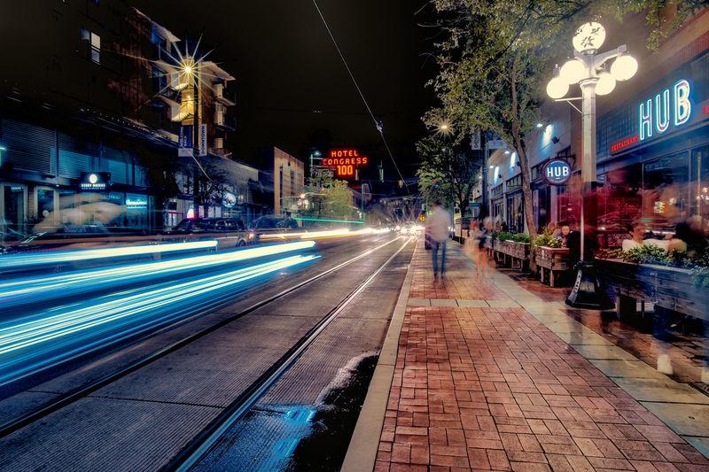 Light trails on sidewalk in city at night