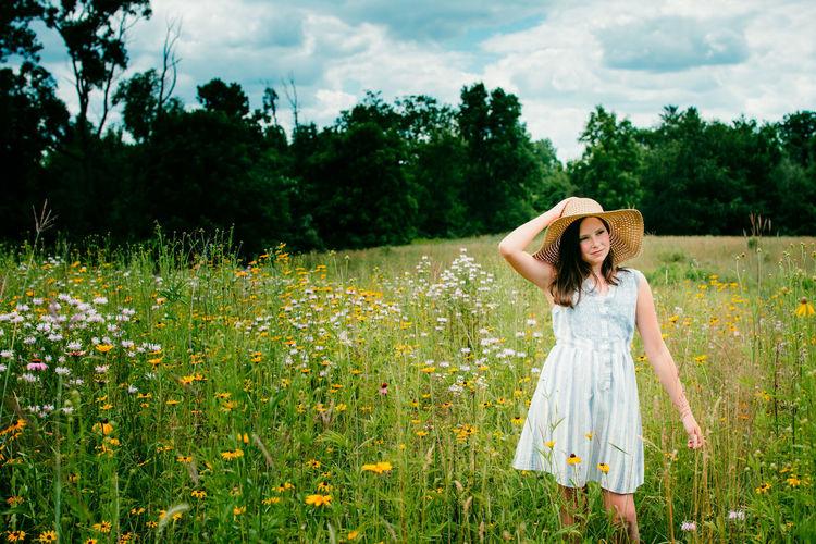 Woman walking among pink flowers in a meadow