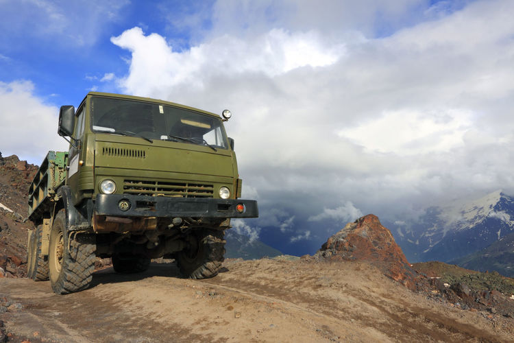 Truck On Mountain Against Cloudy Sky