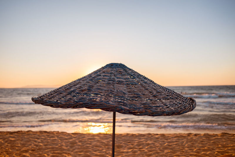 Parasol at beach against clear sky during sunset