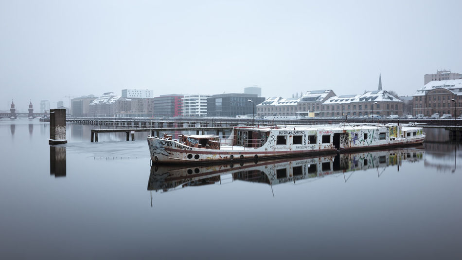 Abandoned shipwreck at Berlin East-Harbor Abandoned Ship Architecture Berlin Berlin East Harbor Berlin Mediaspree Bridge - Man Made Structure City Cityscape Clear Sky Day Fineart Longexposure Muted Colors Nautical Vessel No People Outdoors Philipp Dase Reflection Sky Spree River Berlin Urban Skyline Water Winter 2017 Winter In The City Discover Berlin