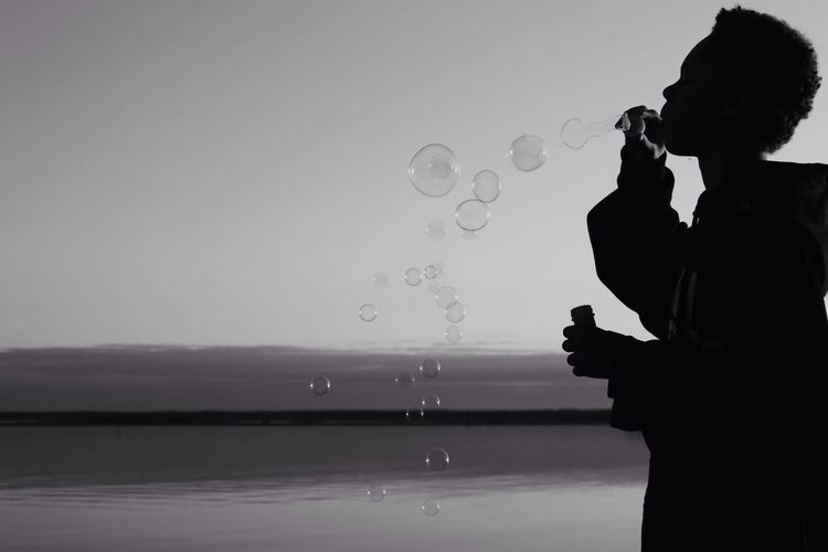 Silhouette Boy Blowing Bubbles At Beach Against Sky