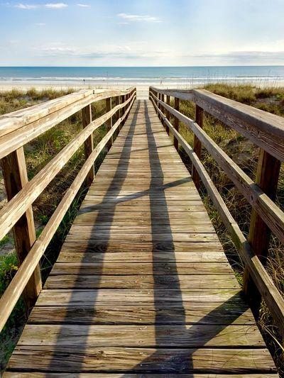 Wooden boardwalk leading towards sea against sky