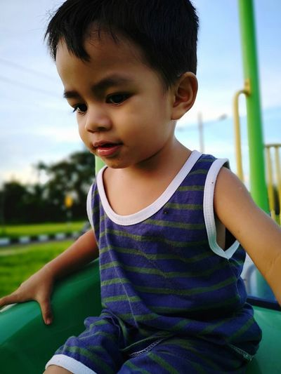Low angle view of cute boy on slide