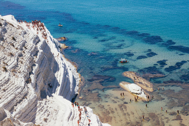 High angle view of people on cliff by sea