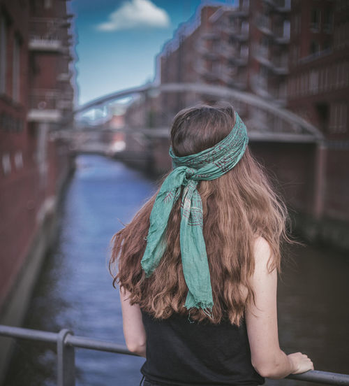 Rear view of woman standing by railing in canal