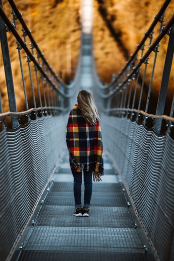Rear view of young woman standing on footbridge in forest during autumn