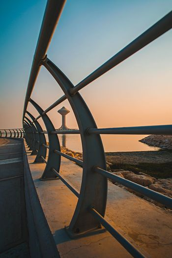 Metal railing by sea against clear sky during sunset