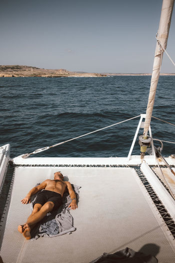 Man relaxing on boat in sea against sky