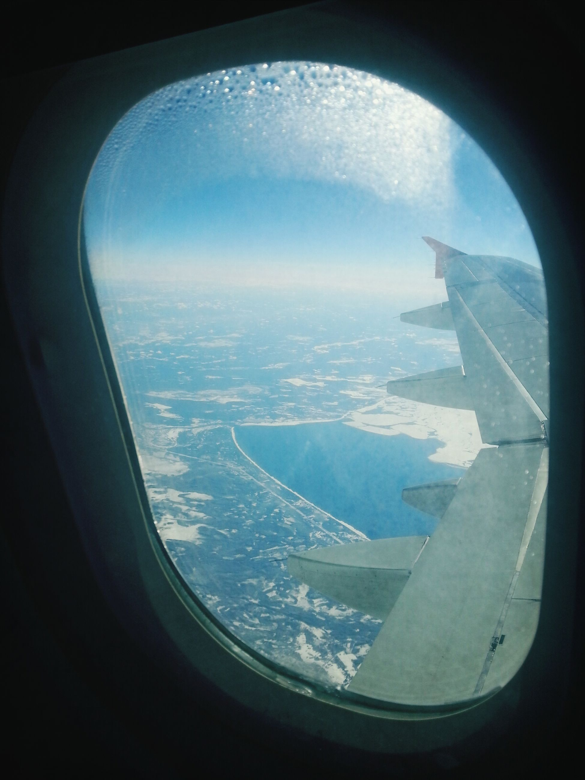 airplane, air vehicle, window, transportation, aerial view, vehicle interior, aircraft wing, mode of transport, flying, transparent, glass - material, sky, indoors, travel, part of, journey, mid-air, looking through window, cropped, landscape