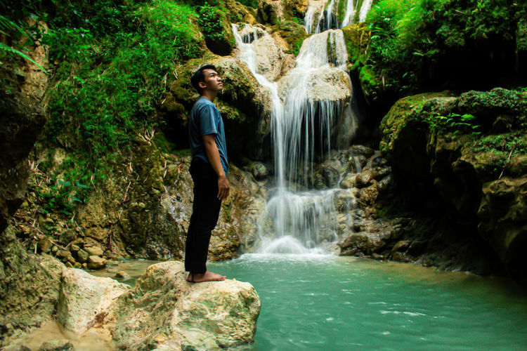 Scenic view of waterfall in rainforest with young asian man standing in profile view