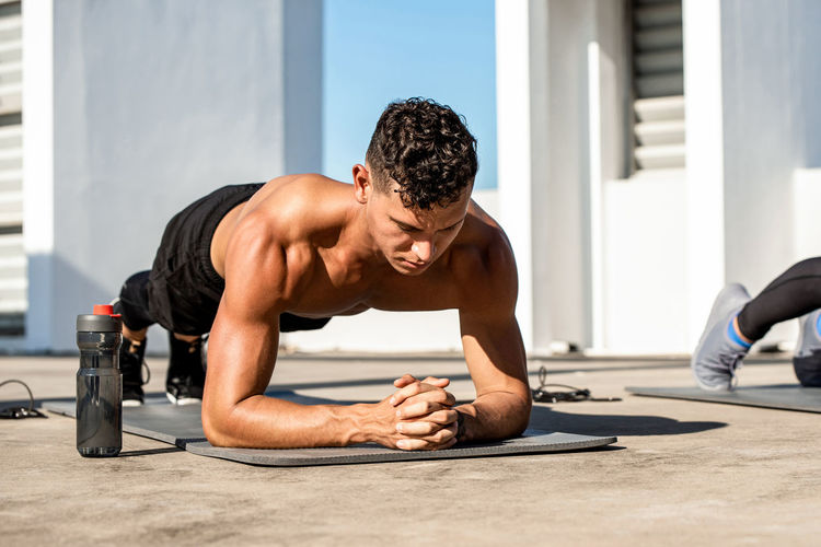 Full length of shirtless man exercising outdoors