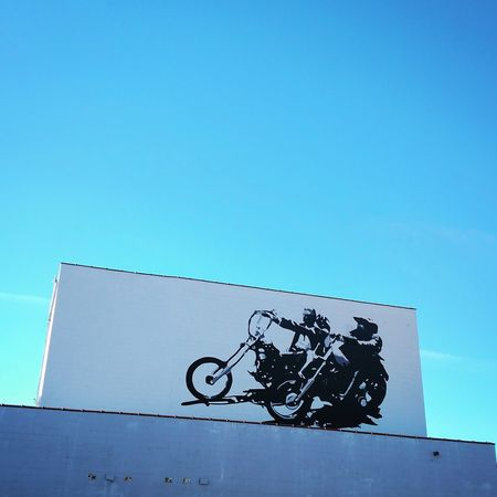 Motorcycles on the side of the building. No People Clear Sky Sky Day Outdoors Sky And Clouds Kansas Cloud - Sky Journey The Way Forward Motorcycle Motorcycles Motorcycle Photography Riding My Motorcycle Riding streetart #street #streetphotography #tagsforlikes #sprayart #urban #urbanart #urbanwalls #wall #wallporn #graffitiigers #stencilart #art #graffiti #instagraffiti #instagood #artwork #mural #graffitiporn #photooftheday #stencil streetartistry photograp Streetartphotography