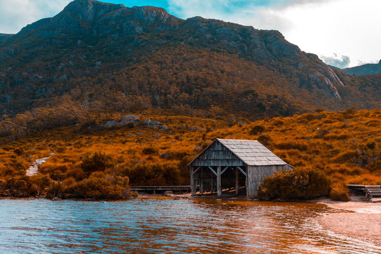 House by lake and mountains against sky