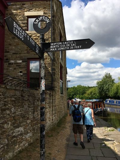Signpost on the Leeds Liverpool canal in Skipton, Yorkshire Towpath Boat Canal Yorkshire Leeds Liverpool Canal Barge Transport Peaceful Lifestyle Town United Kingdom England Skipton Signpost Real People Cloud - Sky Men Architecture Group Of People Sky Built Structure Adult Day Building Exterior Lifestyles Women Leisure Activity People