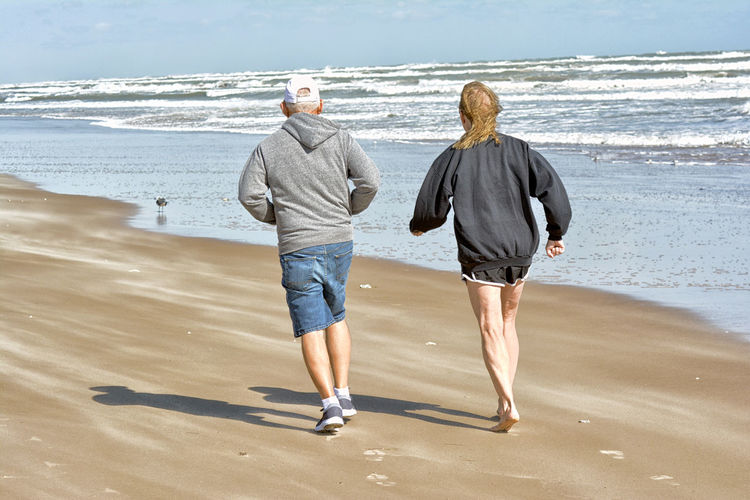 Rear view of couple walking at beach