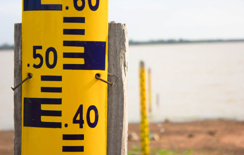 Water level meter Capital Letter Close-up Communication Day Focus On Foreground Guidance Meter Nature No People Outdoors Protection Safety Security Sign Sky Text Warning Sign Warning Symbol Water Western Script Yellow