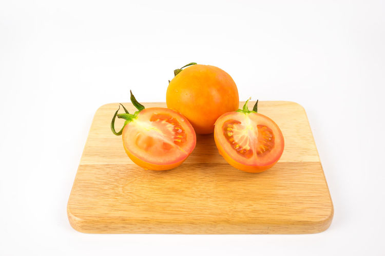 Close-up of fruits on cutting board against white background
